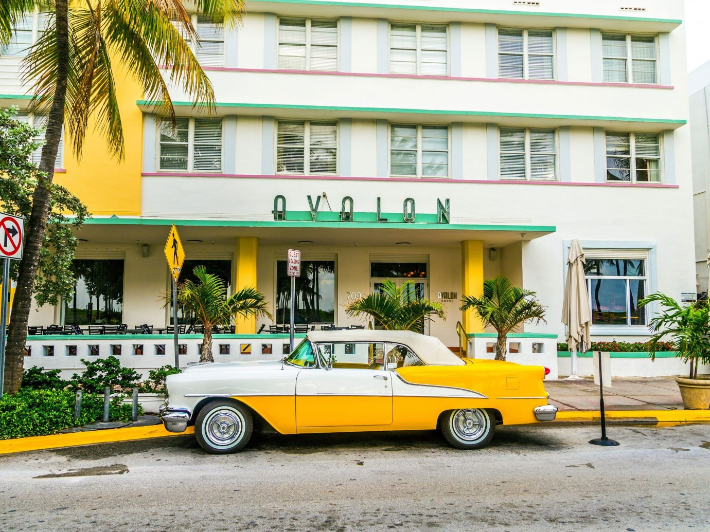 Offbeat outdoor building yellow car vehicle parked road neighbourhood street automobile make infrastructure facade taxi