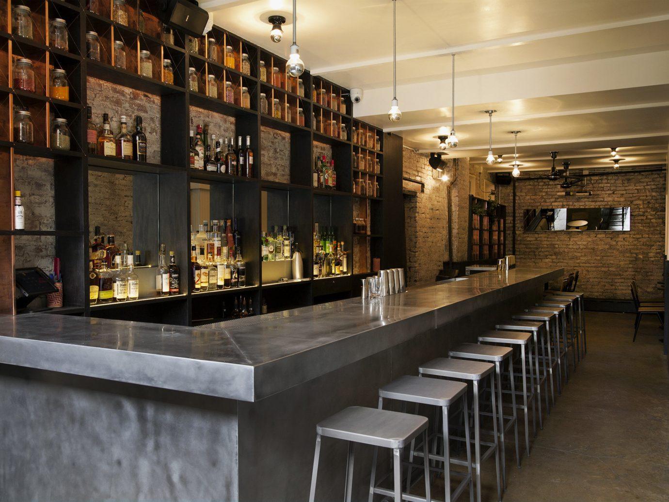 Food + Drink indoor floor interior design Bar liquor store restaurant long lined line several