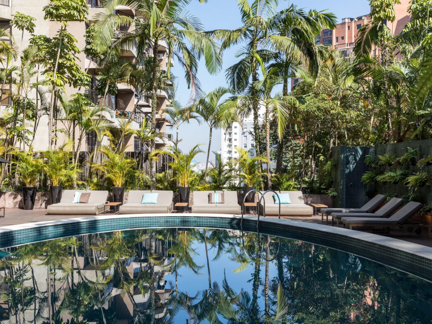 Hotels tree outdoor Resort swimming pool property arecales palm tree real estate estate condominium leisure home water Villa hotel reflecting pool mixed use plant vacation landscaping amenity