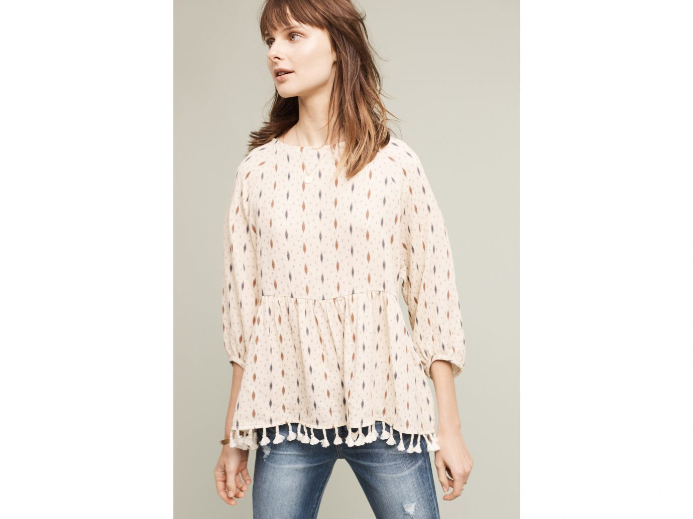 Style + Design person clothing wall standing sleeve indoor outerwear blouse pattern shirt Design posing neck textile collar beige polka dot photo shoot sweater trouser