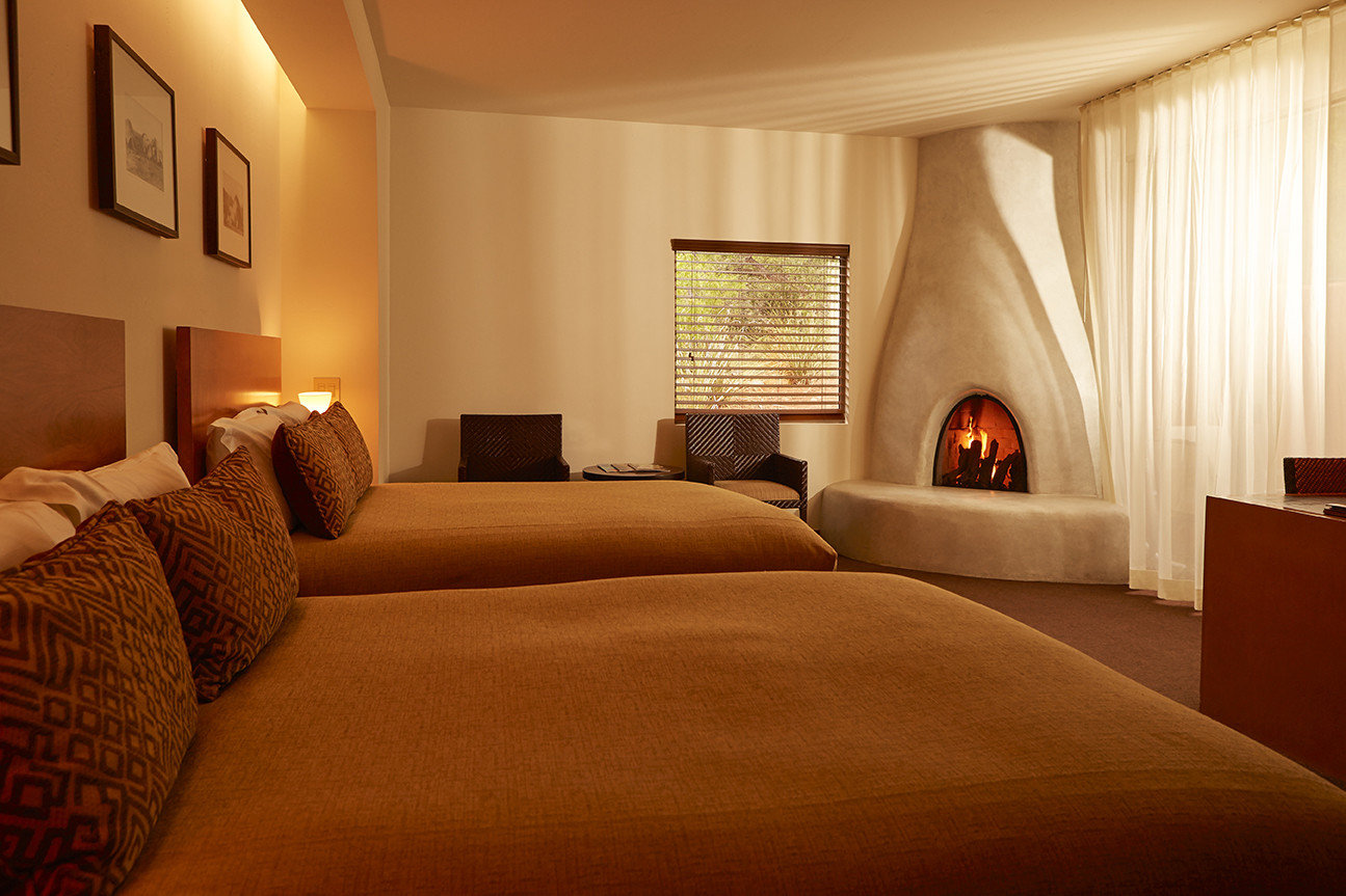 ambient lighting bed Bedroom cozy double Fireplace relaxation Rustic warm indoor wall hotel room ceiling property Suite estate interior design home floor living room