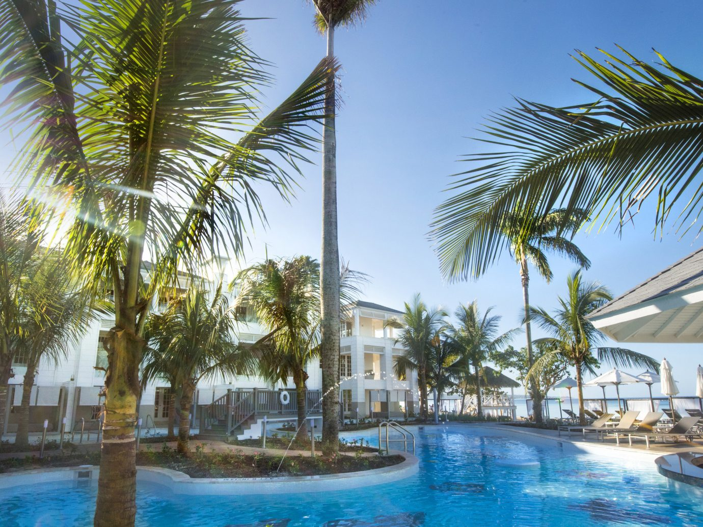 Hotels sky outdoor tree palm Resort Pool property leisure swimming pool caribbean vacation arecales plant resort town Beach palm family Lagoon condominium estate marina lined swimming shade