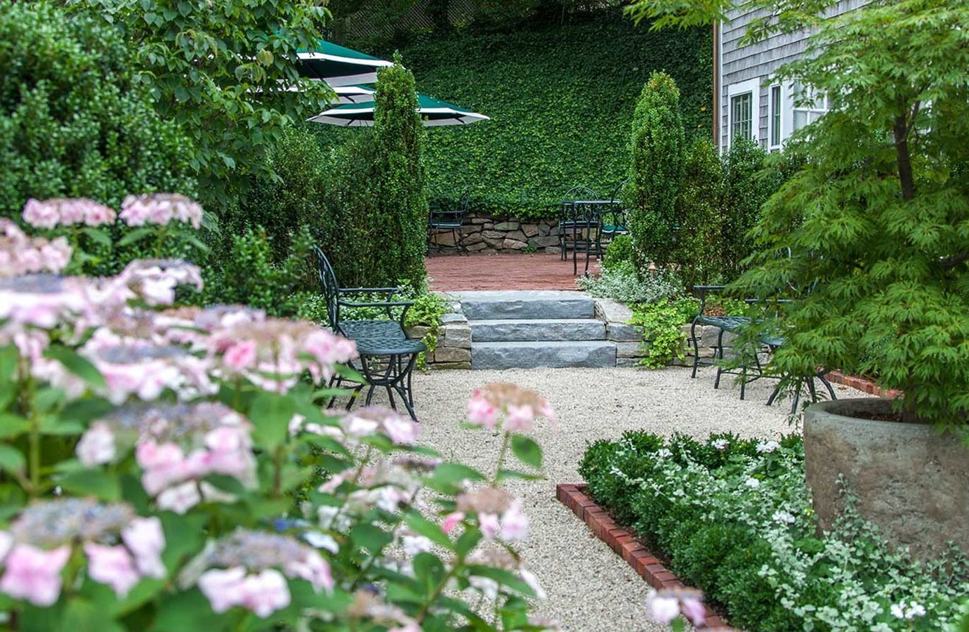 Hotels tree outdoor ground grass Garden flower plant walkway yard flora house backyard botanical garden landscape landscaping groundcover outdoor structure bushes stone Courtyard lawn spring gardening shrub surrounded