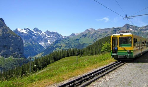 Trip Ideas mountain sky outdoor train track grass transport vehicle mountain range rolling stock green traveling cable car alps