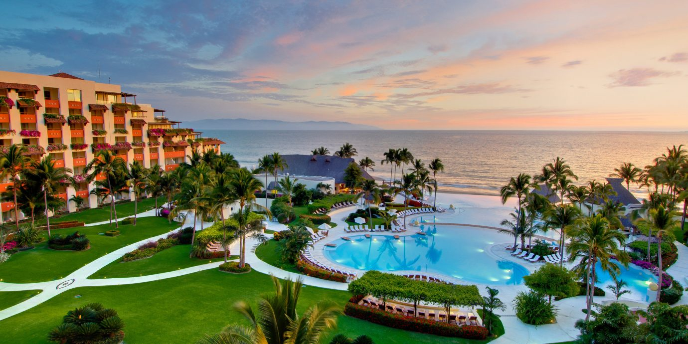 All-Inclusive Resorts Beach Beachfront Exterior Grounds Hotels Pool Resort Romance Sunset Tropical sky grass outdoor vacation green estate bay Sea Coast swimming pool caribbean plant Garden