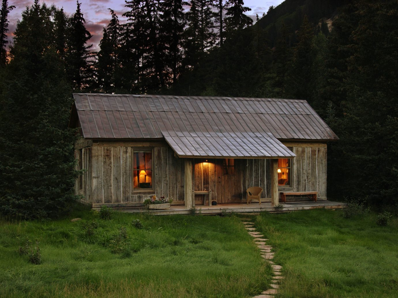 Boutique Hotels Fall Travel Hotels Outdoors + Adventure grass tree outdoor house home cottage property hut log cabin farmhouse building real estate shed rural area Farm landscape sky shack wood green wooden old siding roof estate evening barn facade grassy stone pasture lush hillside surrounded