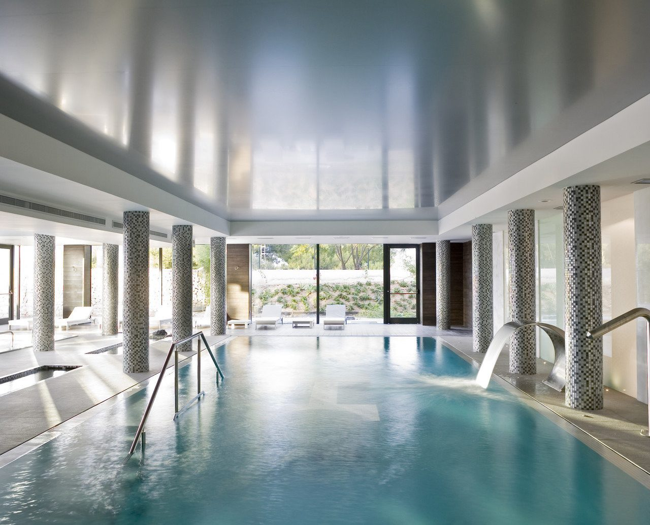 clean Greenery Health + Wellness Hotels indoor pool lounge chairs open-air Pool relaxation Spa Spa Retreats view white swimming pool indoor reflection light Architecture reflecting pool estate lighting headquarters