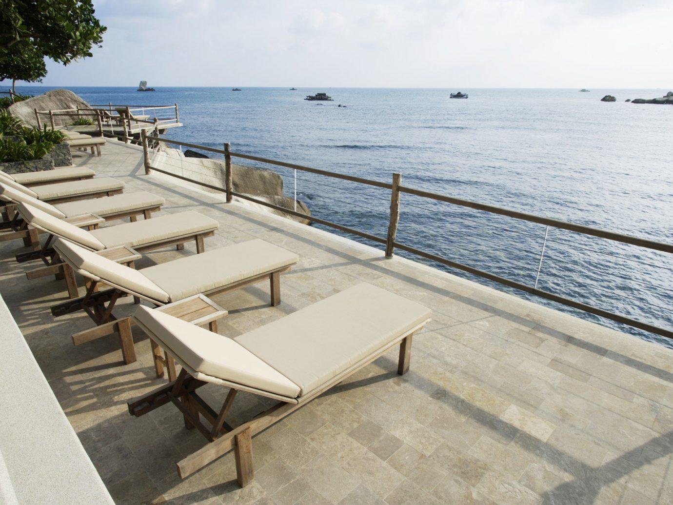 Hotels Luxury Travel sky outdoor water walkway dock Beach Sea shore vacation park Coast Ocean wood boardwalk furniture Resort marina overlooking Deck lined