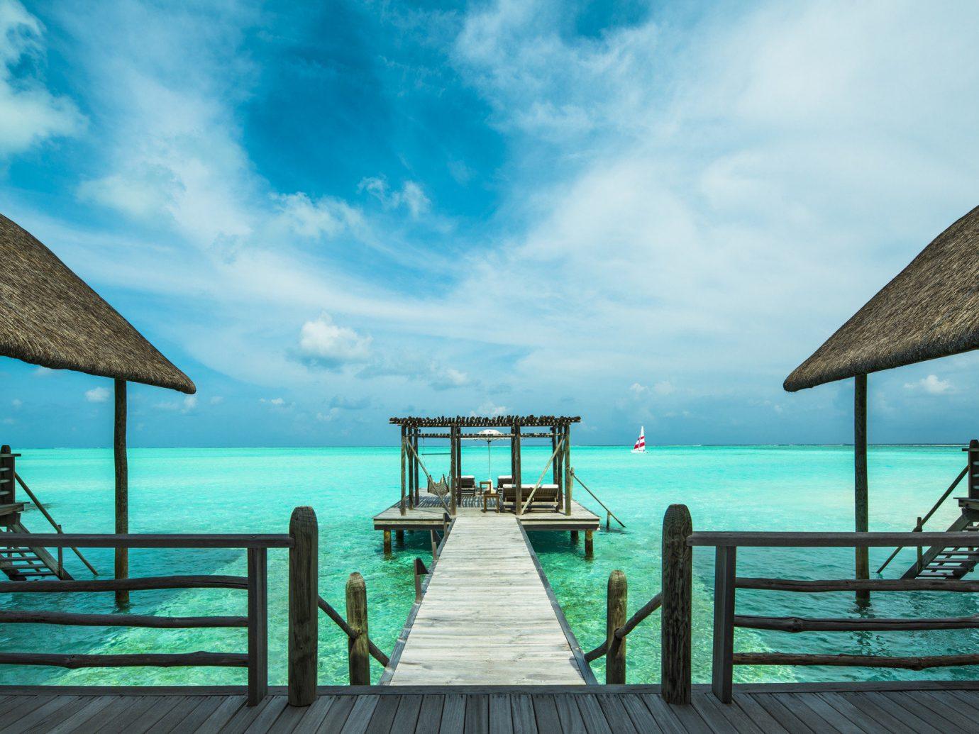 Hotels water outdoor pier sky chair scene umbrella blue Sea Ocean vacation Beach cloud Pool Coast caribbean bay Island empty swimming lined shade