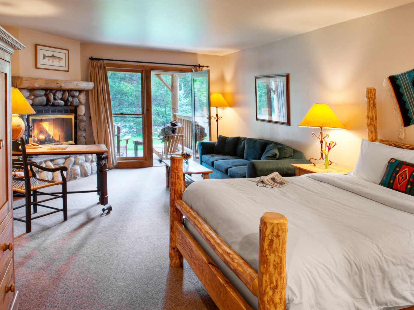 Balcony Bedroom Country Fireplace Glamping Hotels Living Lodge Montana Outdoors + Adventure Patio Ranch Rustic Scenic views Trip Ideas indoor wall room floor bed property estate ceiling home Suite real estate cottage interior design Villa Resort living room furniture wood