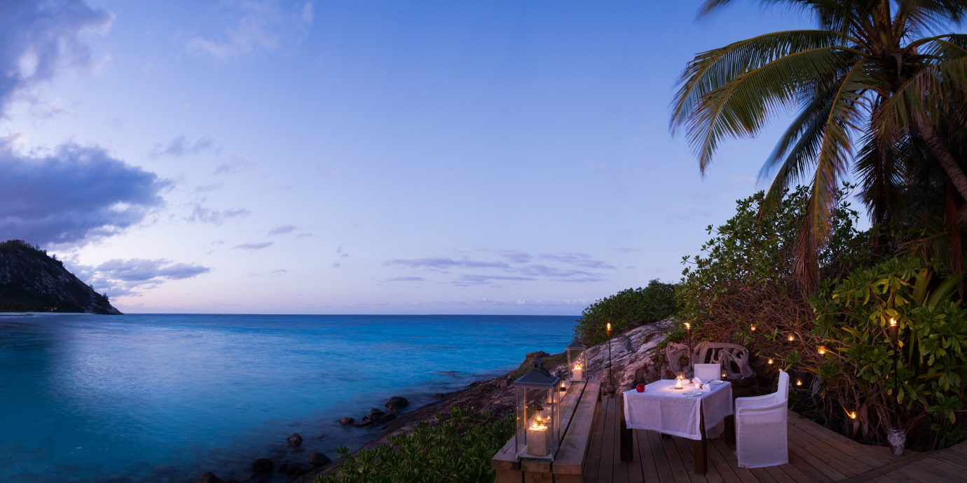 All-Inclusive Resorts Hotels Romantic Hotels sky water outdoor Sea body of water tropics Resort palm tree arecales vacation Ocean tourism tree shore caribbean leisure Beach evening Coast Nature horizon cloud bay Lagoon overlooking