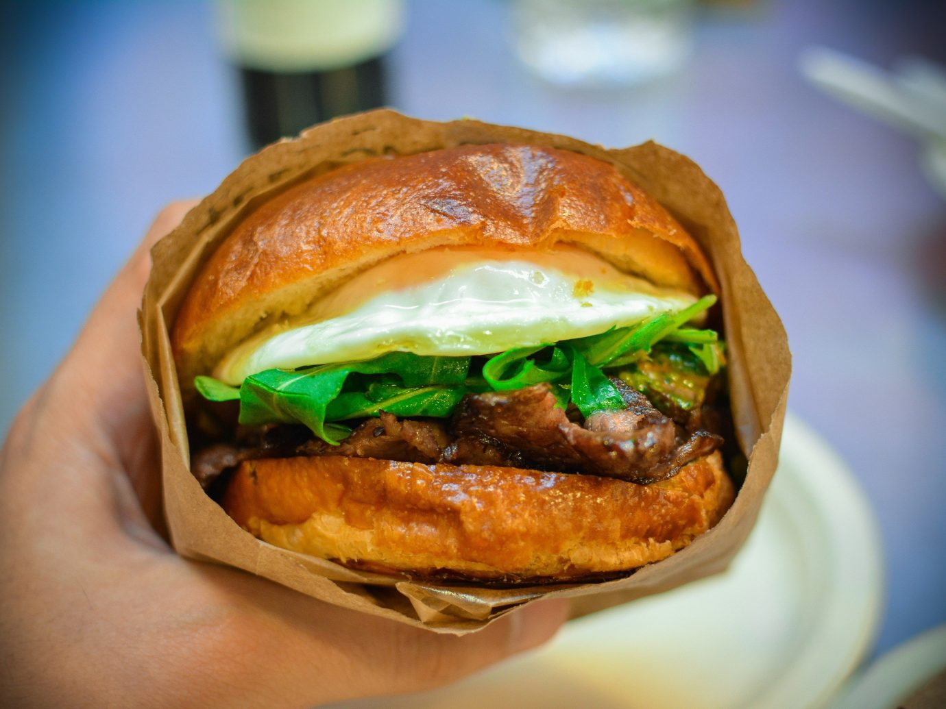 Food + Drink food hamburger person dish indoor snack food cheeseburger veggie burger sandwich bánh mì meal breakfast sandwich slider meat fast food cheesesteak breakfast close