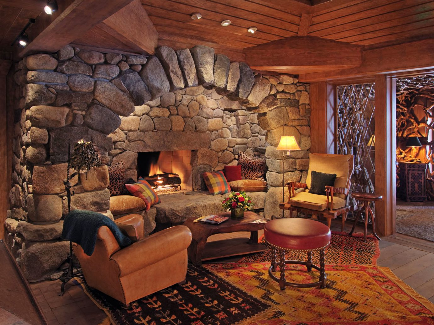 Boutique Hotels Fireplace Hotels Lodge Lounge Outdoors + Adventure Romance Rustic Trip Ideas Waterfront Weekend Getaways indoor floor Living room ceiling living room property furniture estate home cottage interior design hearth log cabin wood farmhouse area