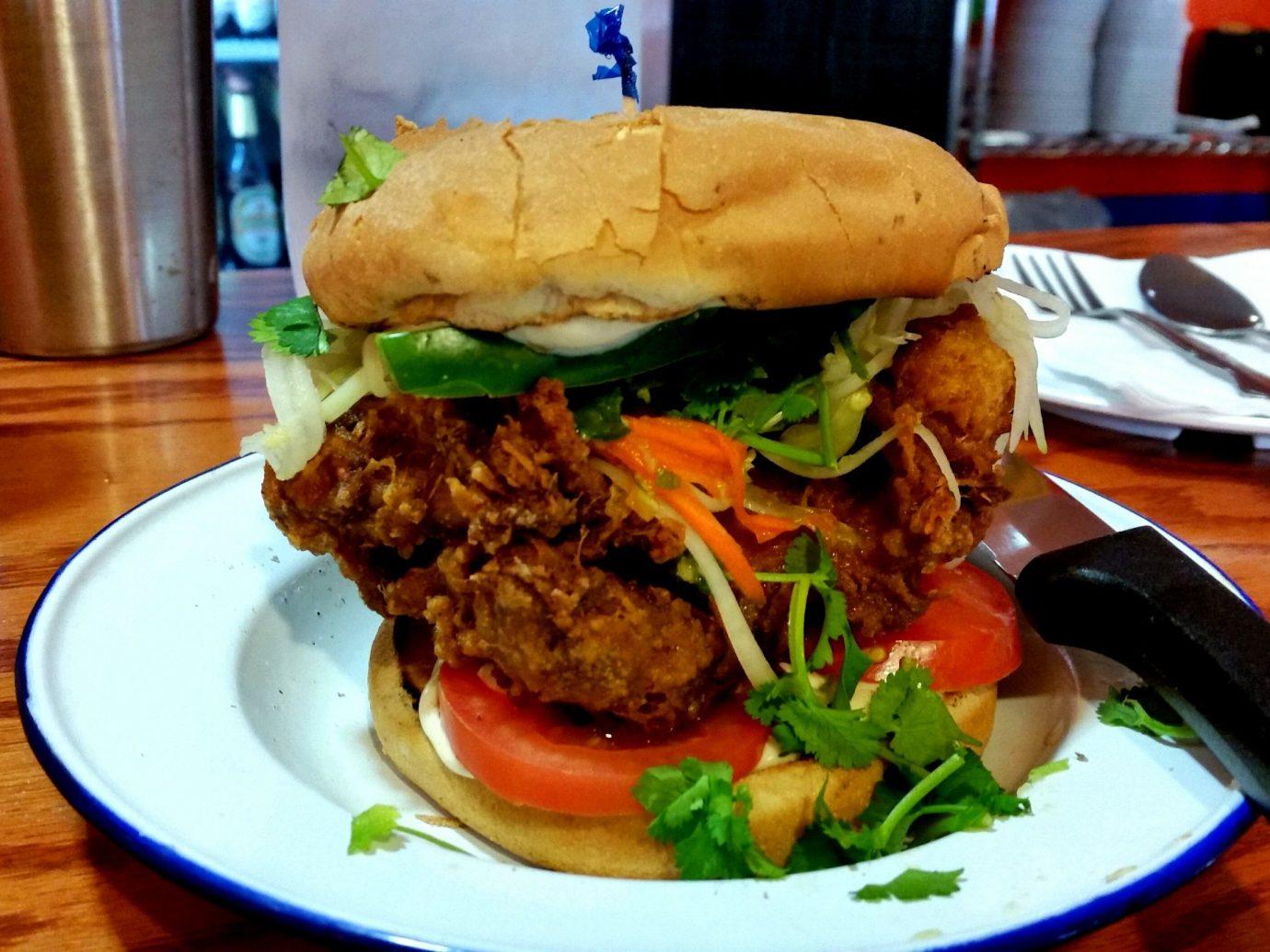 Food + Drink table food plate dish hamburger indoor lunch veggie burger meal restaurant meat sandwich snack food fast food produce fried food breakfast cuisine piece de resistance