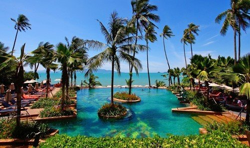 Jetsetter Guides tree sky palm outdoor water Beach umbrella Resort property plant caribbean leisure Pool lined swimming pool arecales resort town Lagoon bay estate real estate lawn sandy shade surrounded swimming