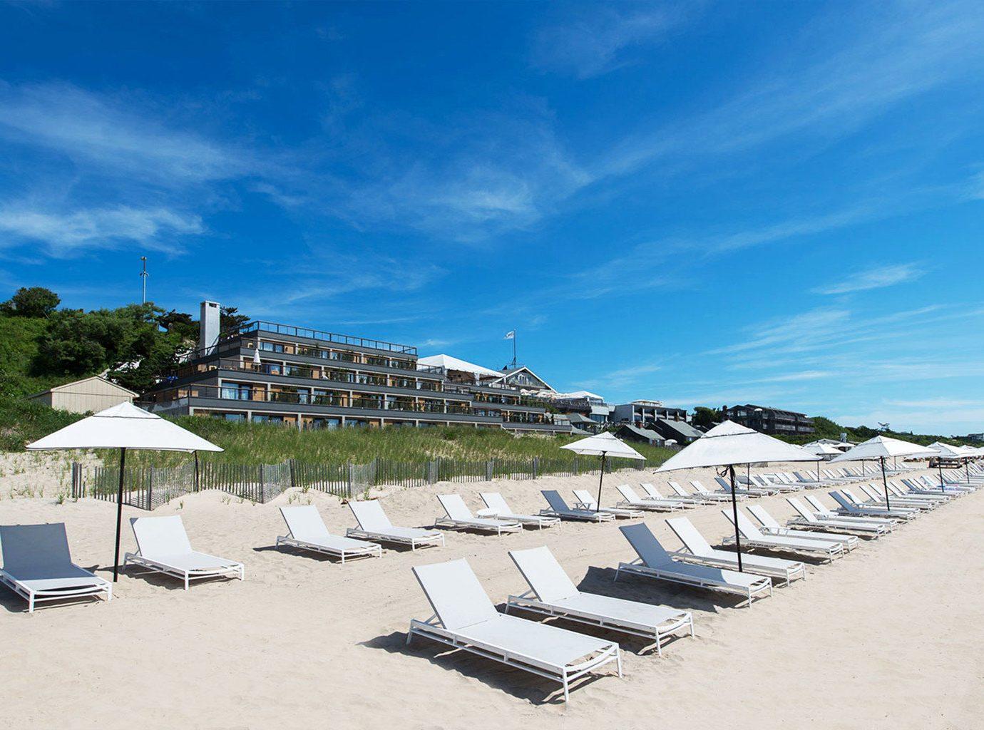 Beach Exterior Hotels Resort outdoor sky umbrella chair Sea Coast vacation shore Ocean lawn walkway bay dock marina boardwalk cape day sandy sunny lined shade several