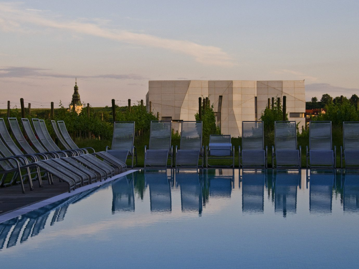 calm dawn dusk europe Health + Wellness Hotels lounge chairs outdoor pool Pool reflection serene Spa Retreats sky outdoor water horizon morning atmosphere of earth reflecting pool River evening overlooking sunlight skyline cityscape Lake reservoir day line