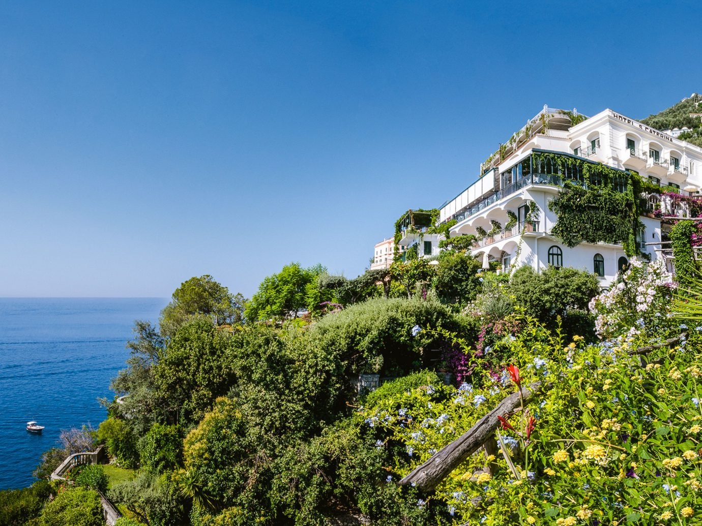 Hotels Romance tree outdoor sky Sea Coast building promontory plant real estate terrain mount scenery house water tourism estate mountain home Resort cottage City bay landscape cape vacation Ocean Village cliff