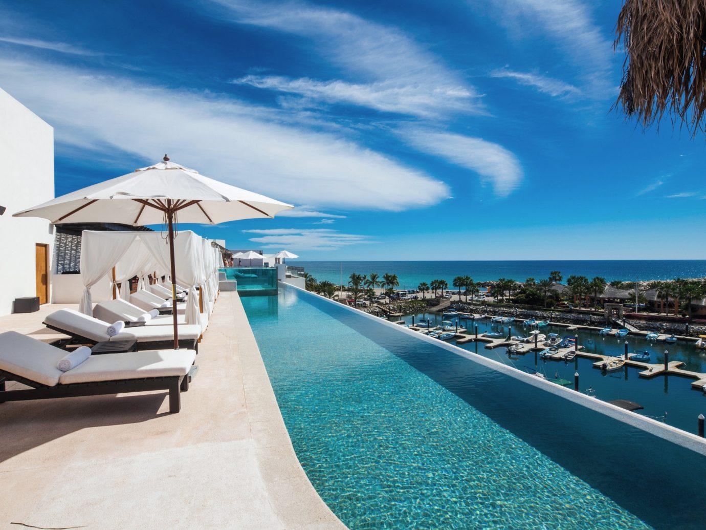 Budget Hotels Luxury Pool Scenic views Waterfront sky outdoor Sea chair Beach vacation Ocean caribbean swimming pool Resort marina estate Coast bay dock Lagoon blue lined shore sandy several