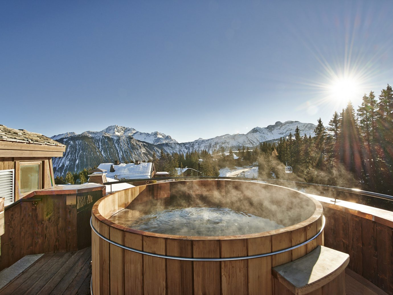 Balcony Hot tub Hot tub/Jacuzzi Hotels isolation jacuzzi Luxury Luxury Travel mountain view Mountains open-air Patio rays remote Rustic snow snow capped Mountains sunlight Terrace trees view Winter sky outdoor swimming pool estate backyard