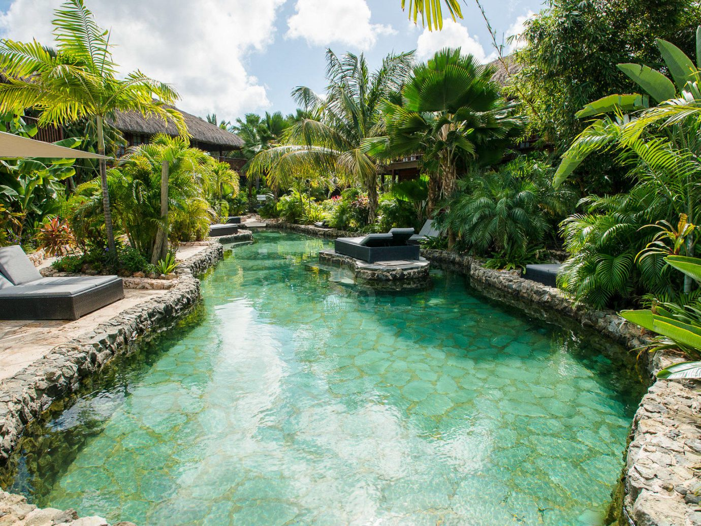 Boutique Hotels Romantic Getaways Romantic Hotels tree outdoor water swimming pool vegetation arecales Resort palm tree tropics Nature leisure plant estate real estate water feature water resources watercourse landscape Lagoon Pool surrounded Garden lined several