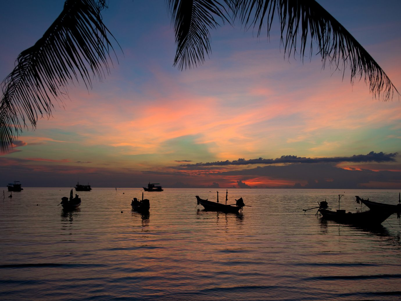 Jetsetter Guides water outdoor sky Sunset horizon sunrise tree reflection Sea dawn dusk cloud evening Ocean morning afterglow shore sunlight palm wave plant Beach