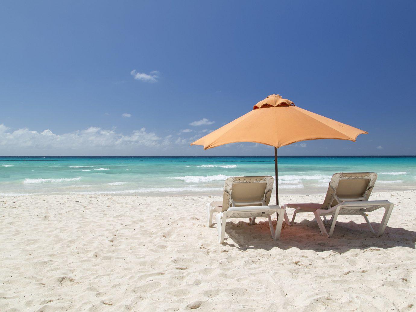 Hotels sky outdoor Beach umbrella water chair shore Nature body of water Sea leisure Ocean vacation caribbean sand Coast Lagoon sun tanning bay Island swimming pool Resort sandy