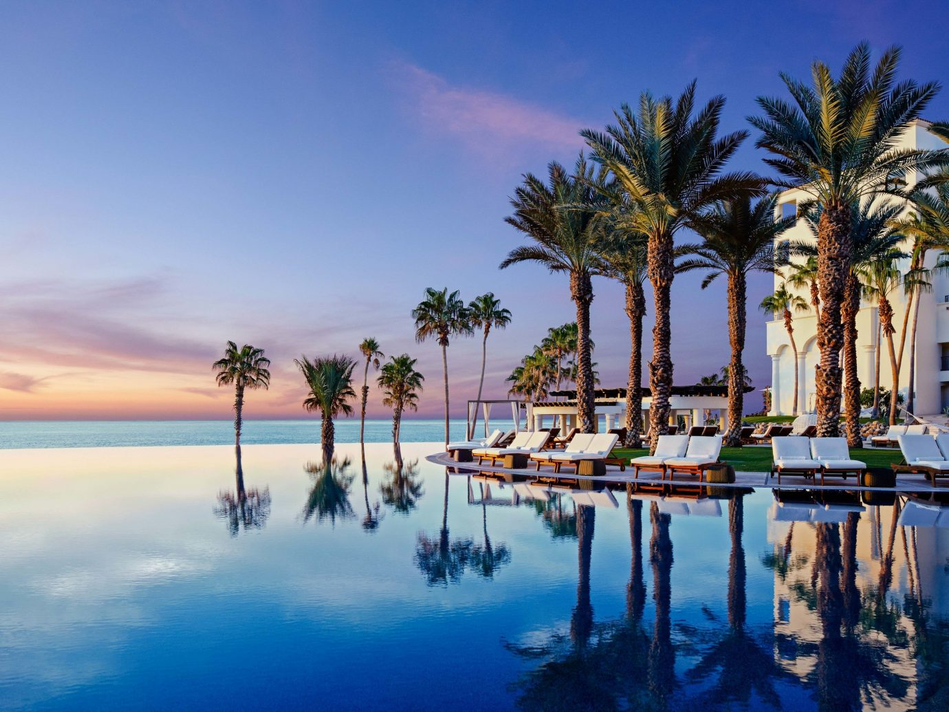Budget Hotels sky outdoor water vacation Resort palm arecales Sea Beach estate Lagoon evening bay reflection swimming pool palm family dusk shore lined