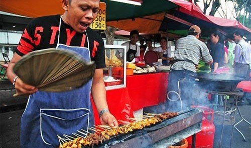 Food + Drink person public space vendor dish food street food market preparing cooking fresh barbecue