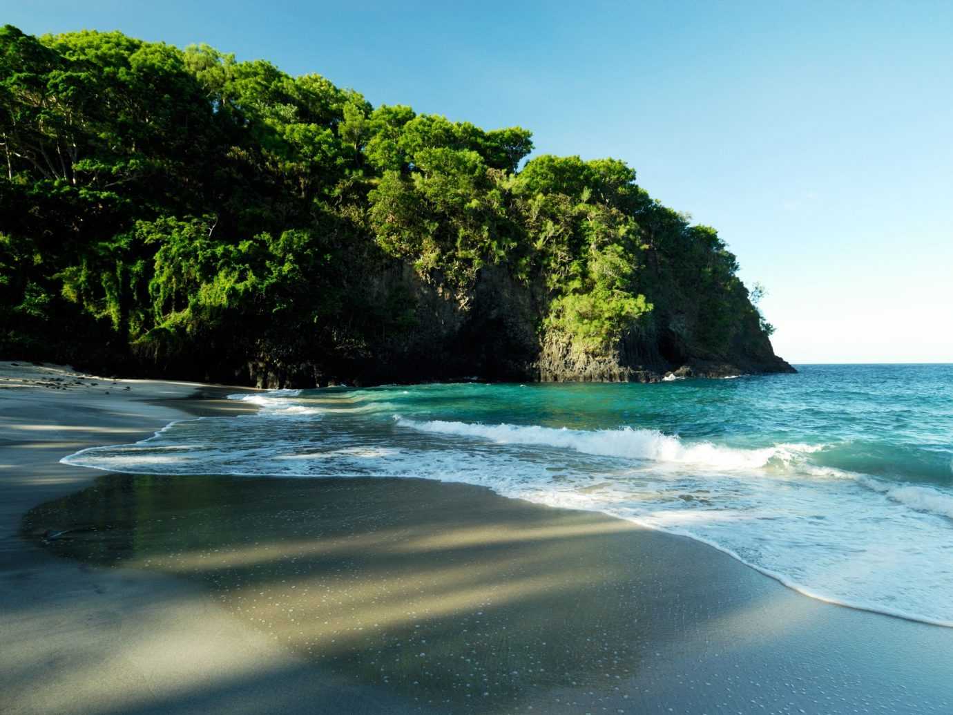 Jetsetter Guides outdoor water sky tree Nature shore landform Sea geographical feature Beach body of water Coast Ocean bay wave islet tropics wind wave rock Island cove Lagoon cape terrain day