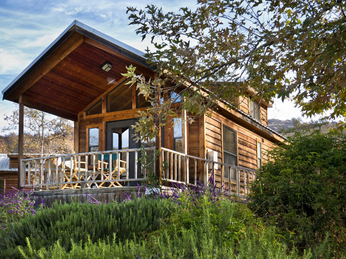Boutique Hotels Fall Travel Hotels Outdoors + Adventure tree outdoor grass house building property home log cabin estate residential area siding cottage shed real estate backyard facade outdoor structure farmhouse yard Garden