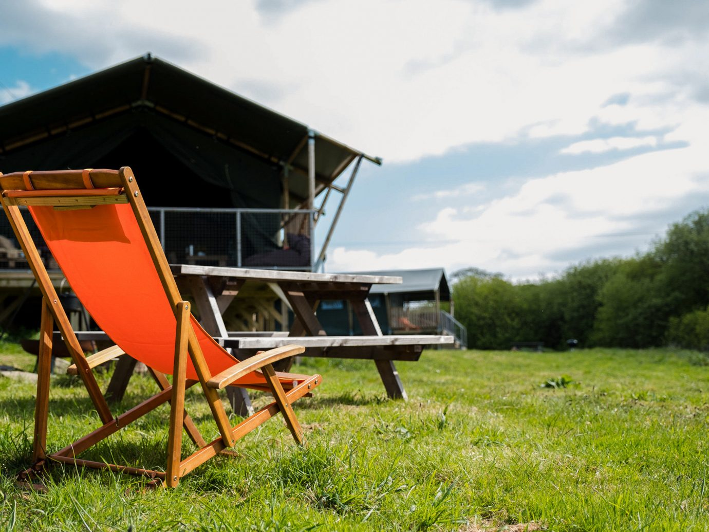 Glamping Outdoors + Adventure Trip Ideas grass sky outdoor plant field rural area tree house meadow landscape chair Farm leisure tent recreation lawn seat