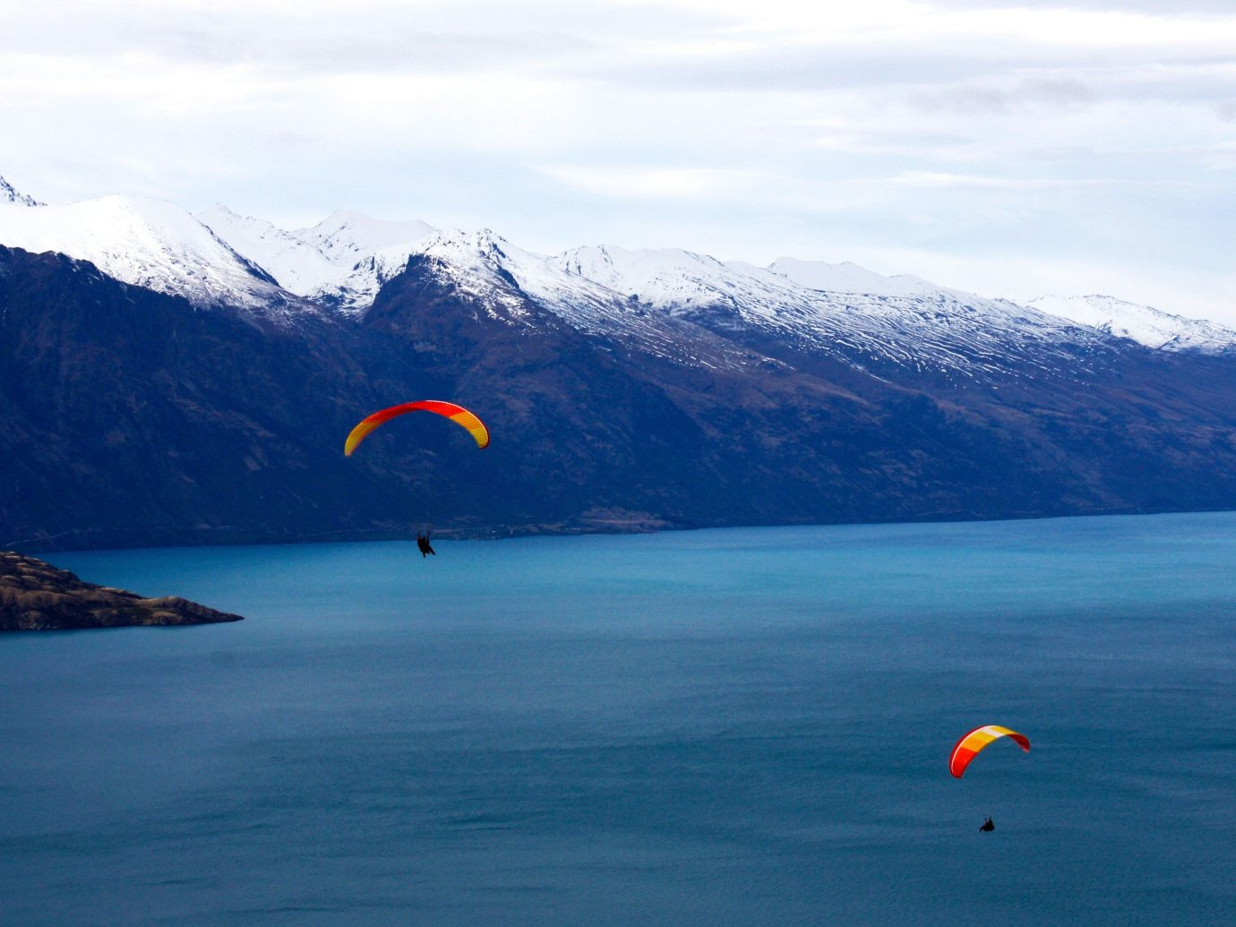 Jetsetter Guides water mountain sky outdoor paragliding air sports Nature sports windsports Lake atmosphere of earth Ocean Sea extreme sport flight mountain range parachuting colorful distance day