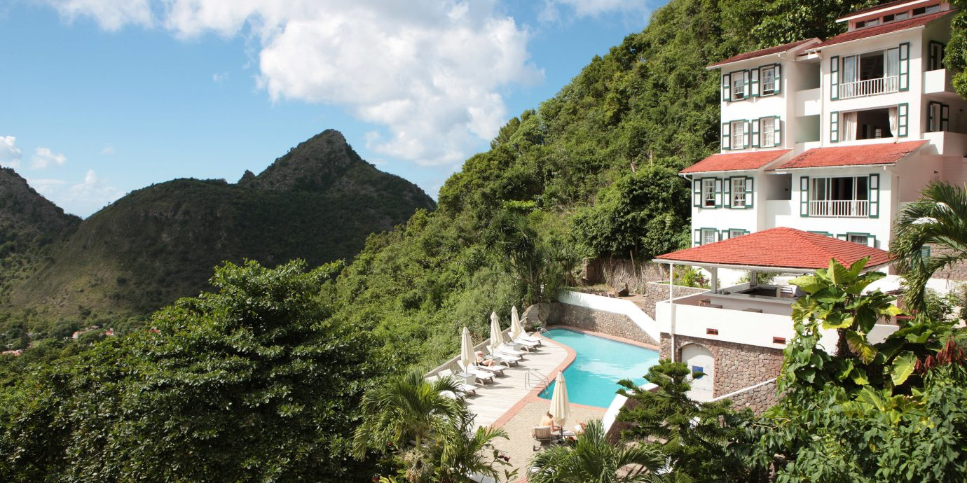 Hotels tree outdoor sky mountain Town vacation estate tourism Resort Village bushes apartment building traveling surrounded