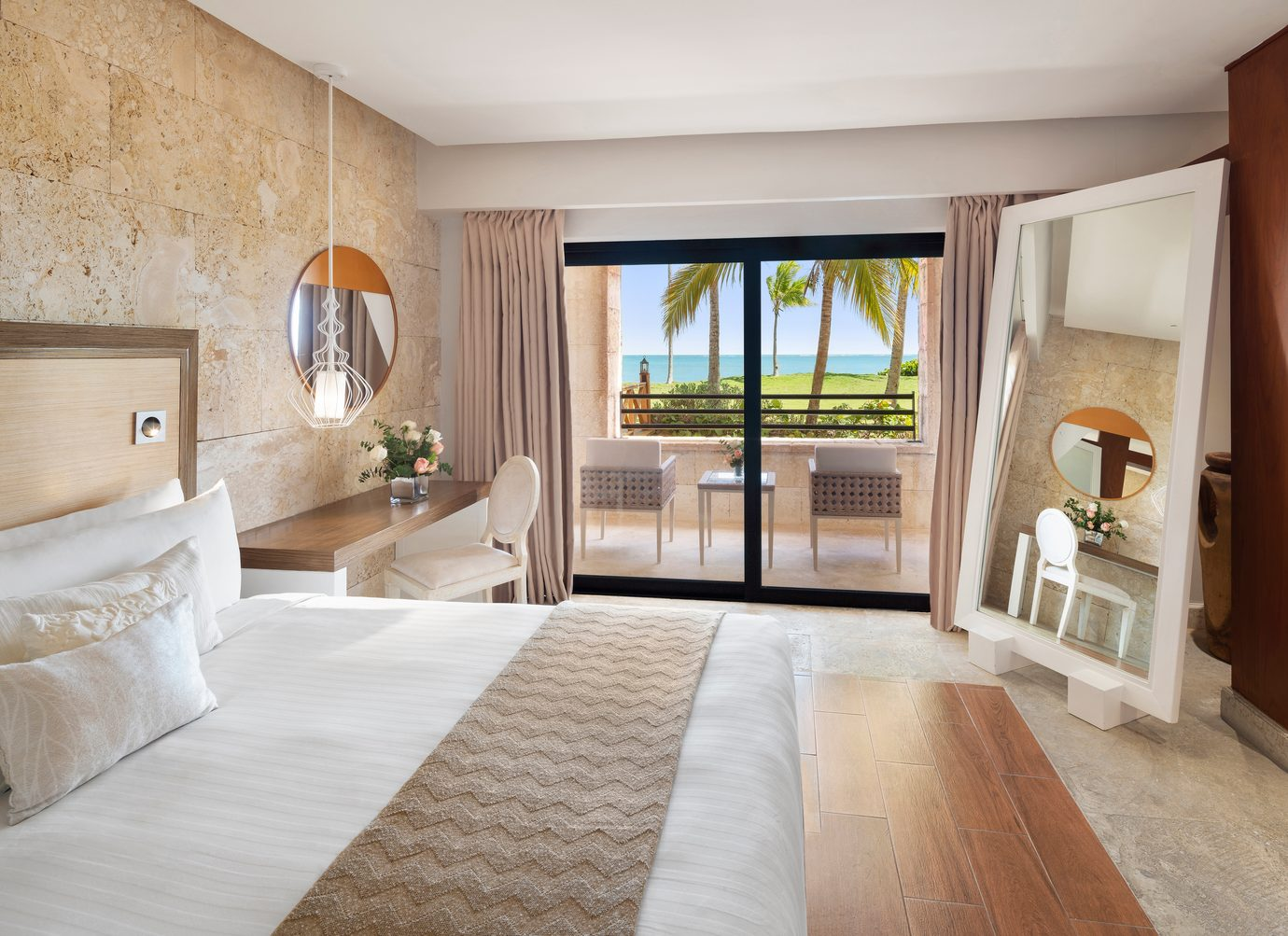 suite with private balcony looking over water and palm trees