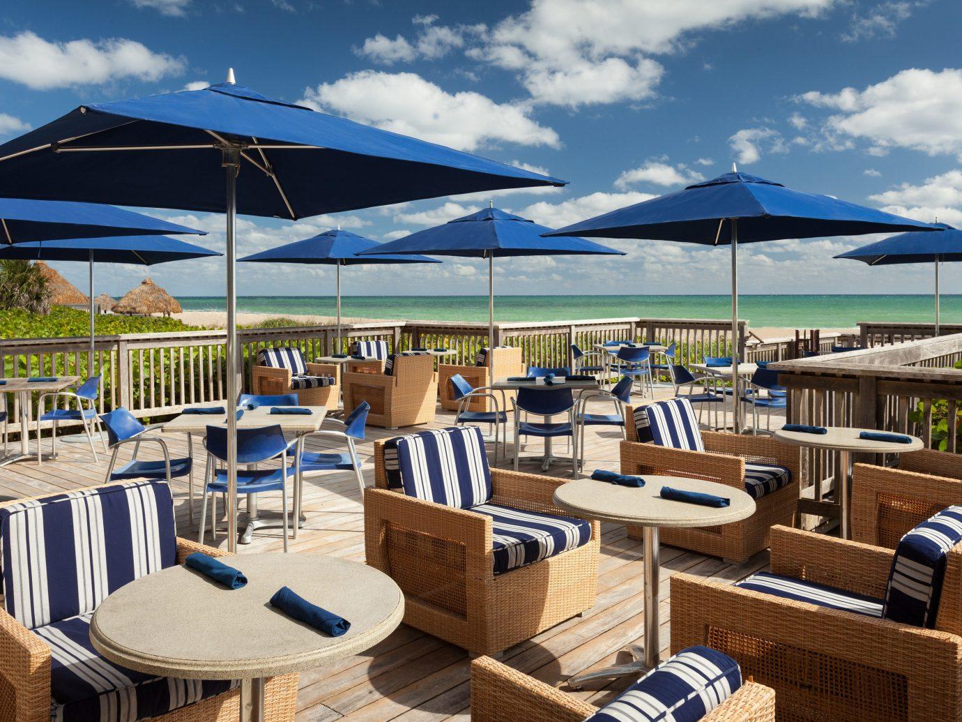 Food + Drink chair umbrella sky outdoor lawn Beach Resort vacation restaurant vehicle marina dock set furniture day Deck shade several