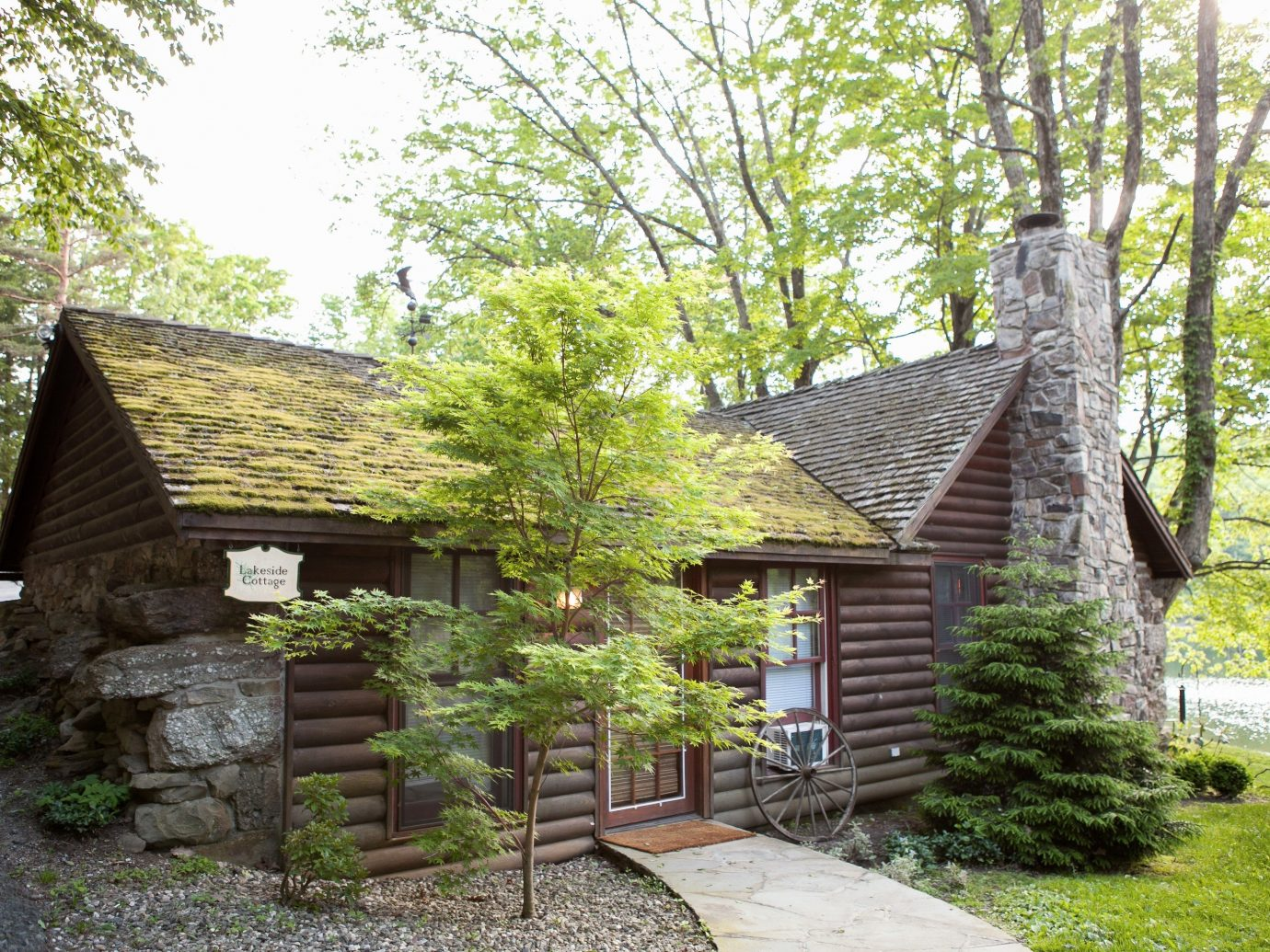 Boutique Hotels Fall Travel Hotels Outdoors + Adventure tree outdoor grass house building property cottage home log cabin real estate farmhouse estate hut historic house stone area Garden wood shade
