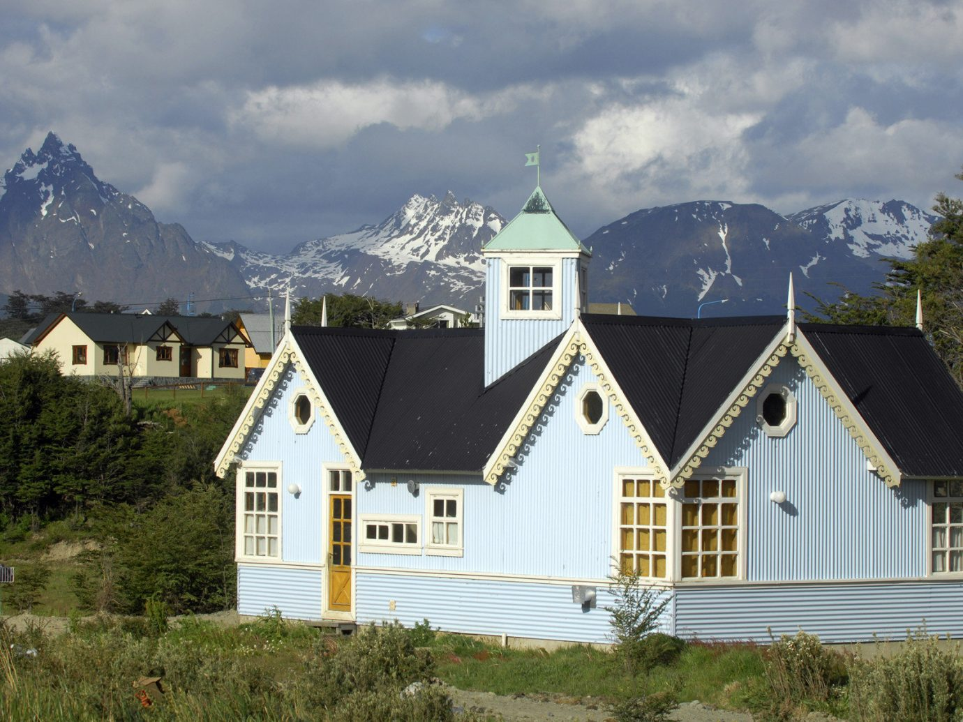 Jetsetter Guides Outdoors + Adventure Packing Tips Travel Tips Trip Ideas mountain outdoor sky grass house building home property cottage background real estate mountain range roof estate hut facade elevation tree window farmhouse alps landscape Town hillside