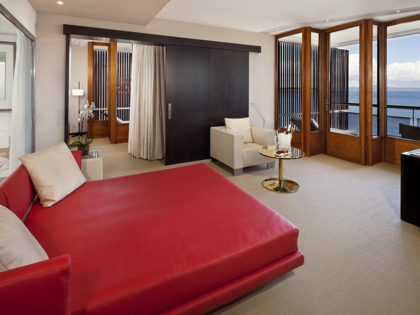 Hotels indoor floor sofa room wall window red property hotel ceiling Suite bed real estate interior design estate living room furniture apartment condominium cottage Bedroom Villa area Modern flat