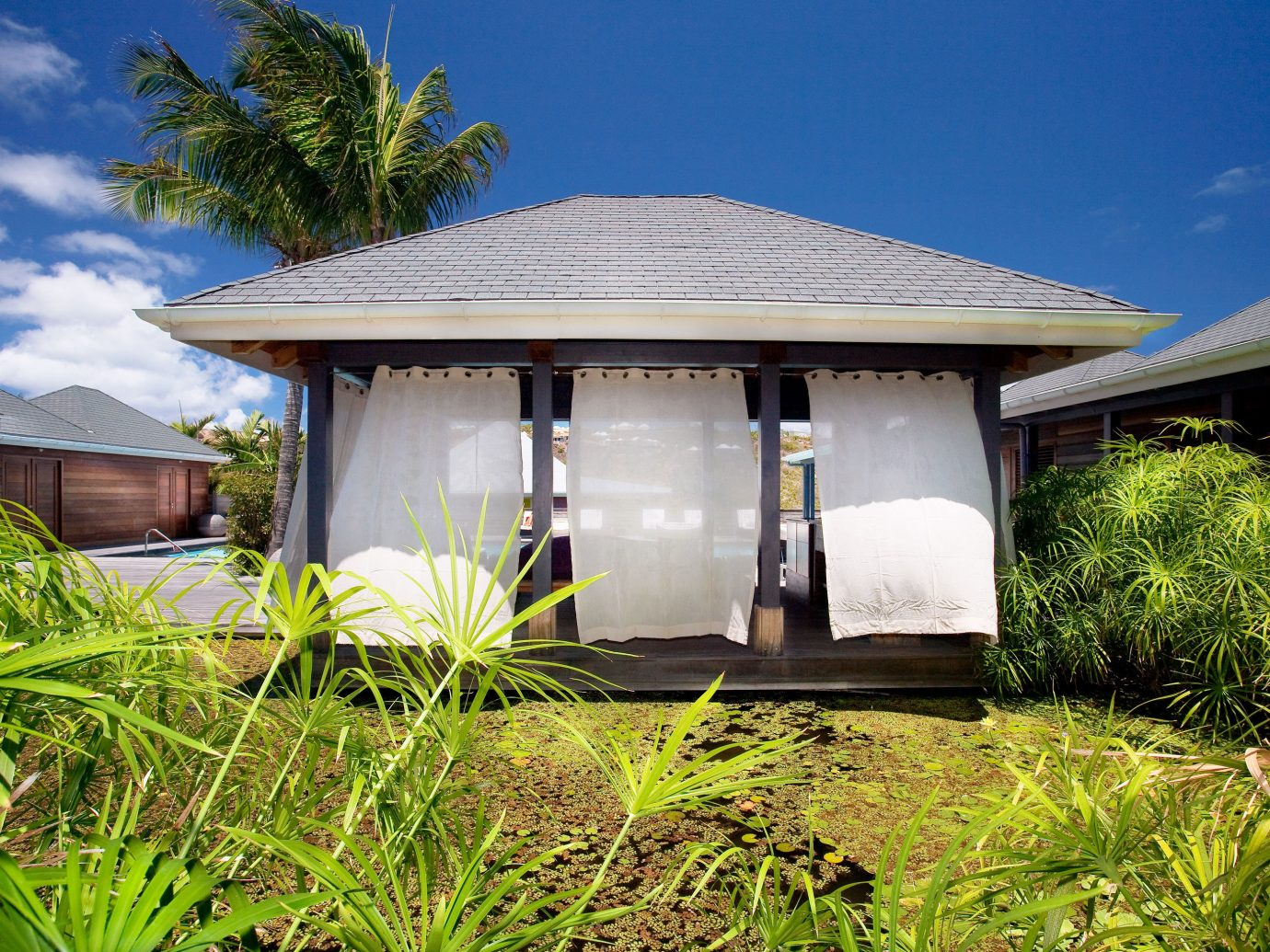 Penthouse Trip Ideas Tropical outdoor grass sky building house home hut estate cottage rural area shack real estate backyard shed Villa outdoor structure