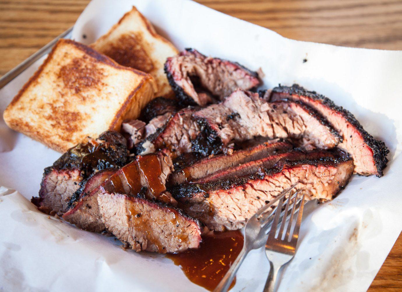 Food + Drink food plate table dish meat piece slice meal roasting steak fork grilling brisket produce breakfast animal source foods cuisine pork dessert sliced barbecue