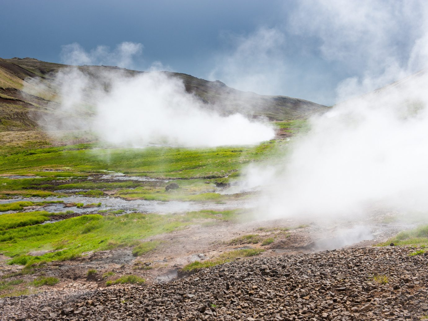 outdoor Nature sky spring ground grass geographical feature landform body of water atmospheric phenomenon wilderness water geyser mountain landscape rock dirt smoke water feature stream Sea