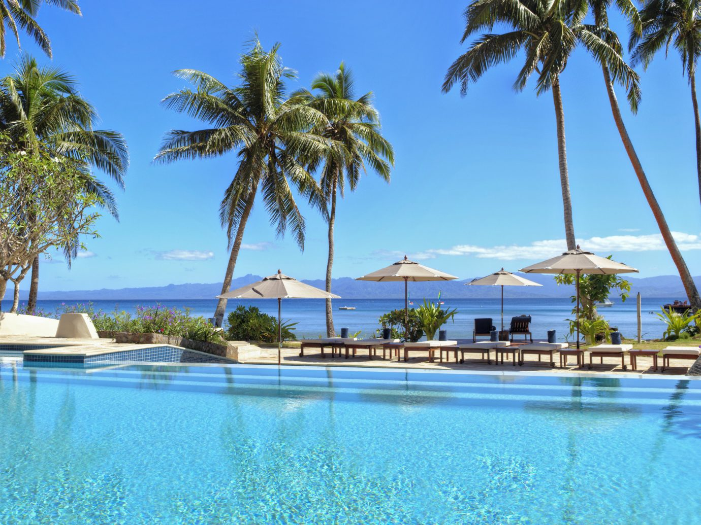 All-Inclusive Resorts Hotels Luxury Travel tree palm outdoor water sky Pool Resort Beach swimming pool property leisure resort town palm tree estate caribbean tropics real estate arecales vacation Villa Sea tourism bay hotel Lagoon plant swimming lined shore shade sandy surrounded