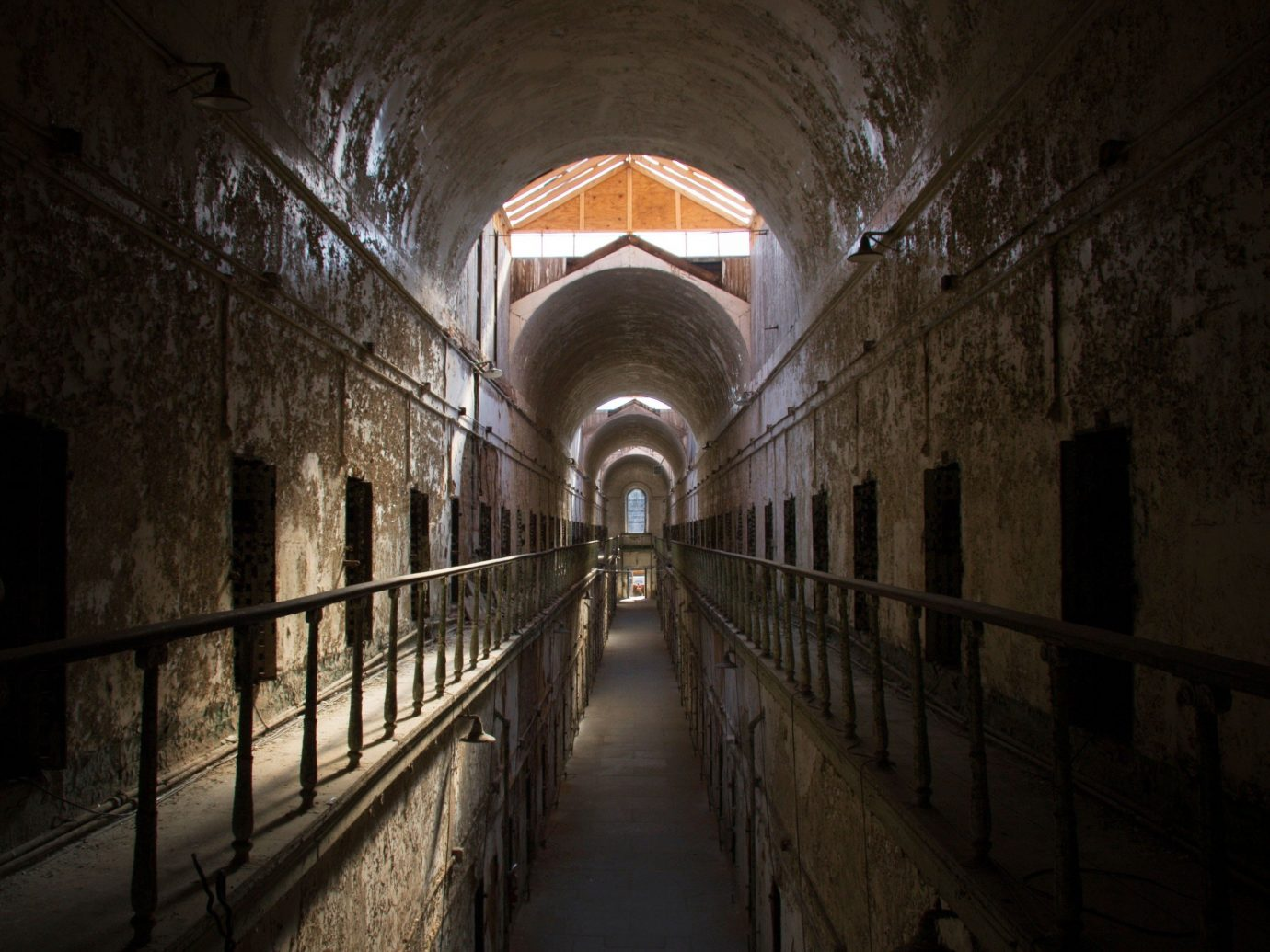 Offbeat night darkness light building tunnel symmetry crypt railing stair walkway