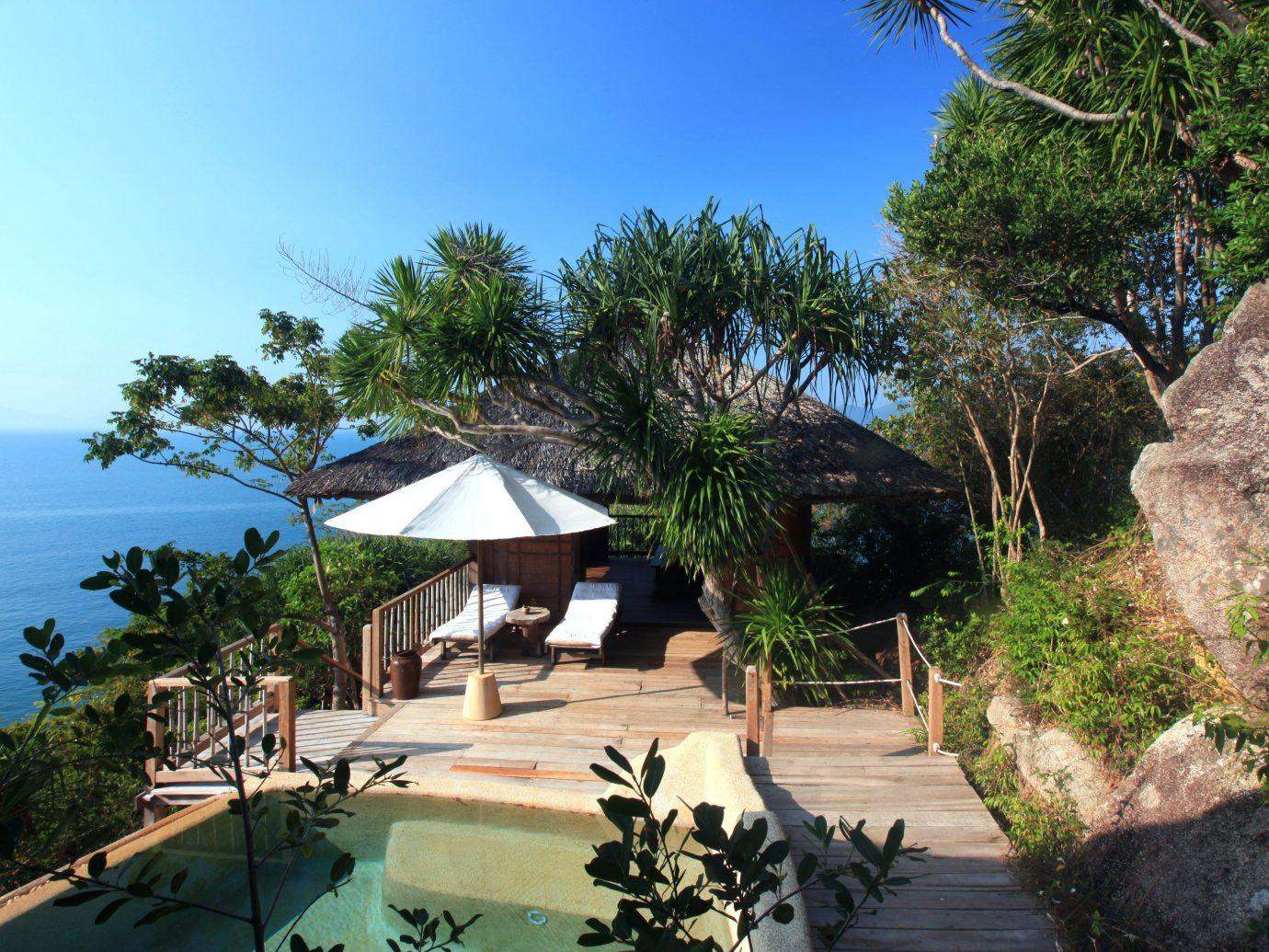 Hotels tree outdoor sky property Resort vacation palm estate plant tourism arecales Beach tropics Villa Village Jungle Sea bay