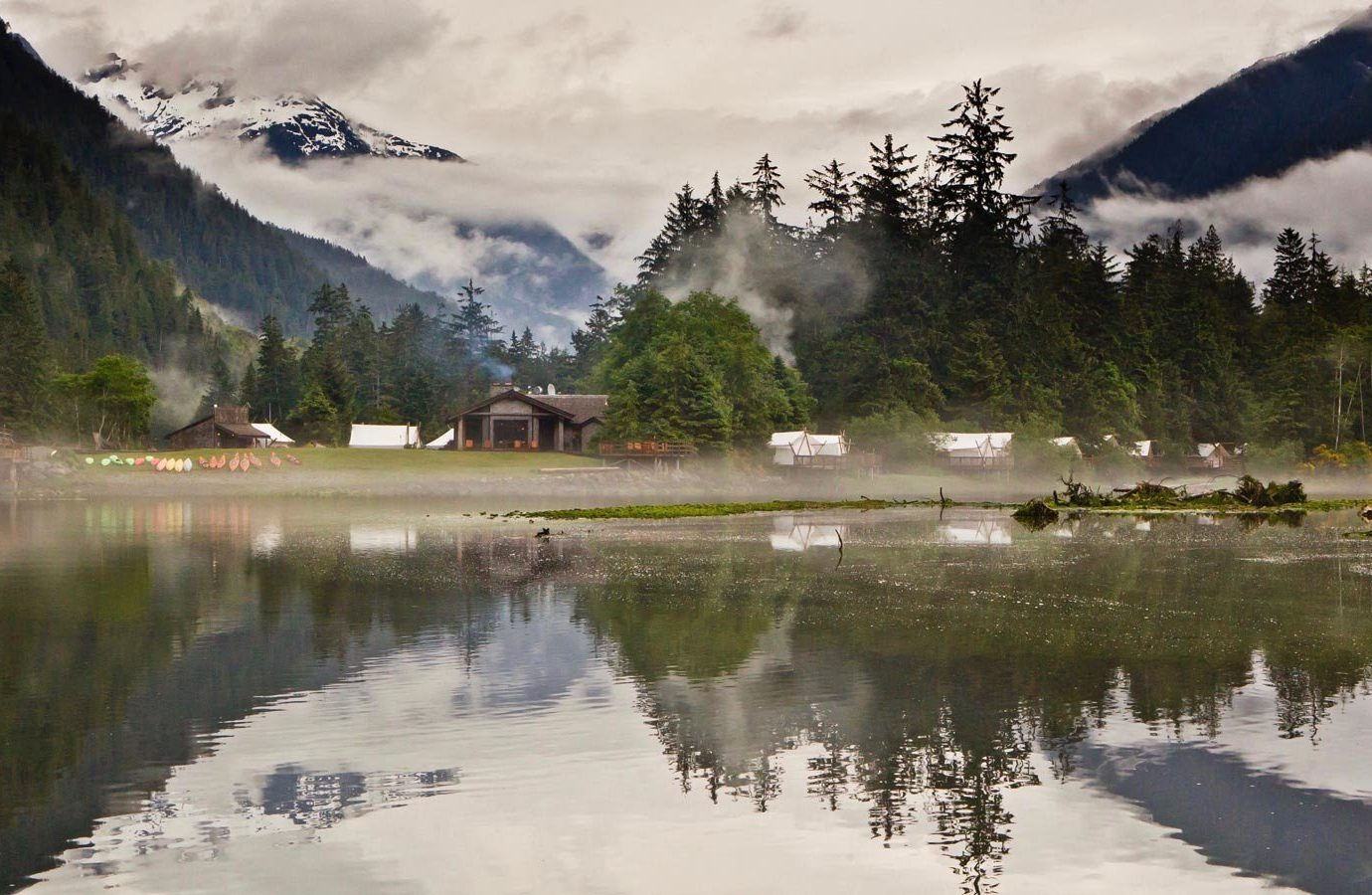 Glamping Luxury Travel Outdoors + Adventure Trip Ideas Weekend Getaways outdoor water Nature reflection mountainous landforms mountain Lake sky wilderness cloud tree pond mountain range morning bank landscape River Winter plant mount scenery loch alps surrounded hillside