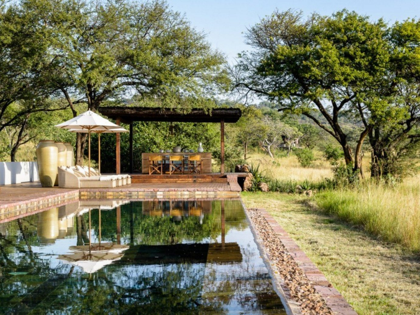 africa calm Greenery lounge chairs Luxury Nature outdoor pool Outdoors Pool private remote Safari serene sophisticated Style + Design trees tree outdoor grass property building park estate River waterway real estate Garden Canal flower cottage Villa pond surrounded