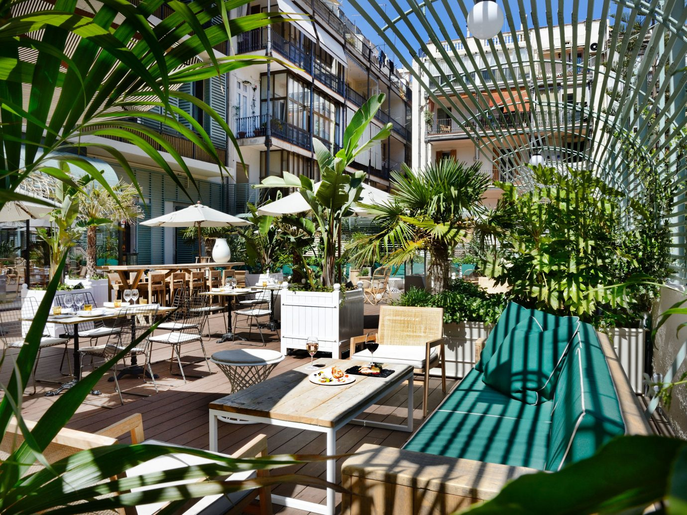 Barcelona Hotels Spain Trip Ideas table tree outdoor plant chair Dining Resort green estate backyard arecales Garden Courtyard home condominium Jungle outdoor structure yard tropics swimming pool palm family restaurant furniture set
