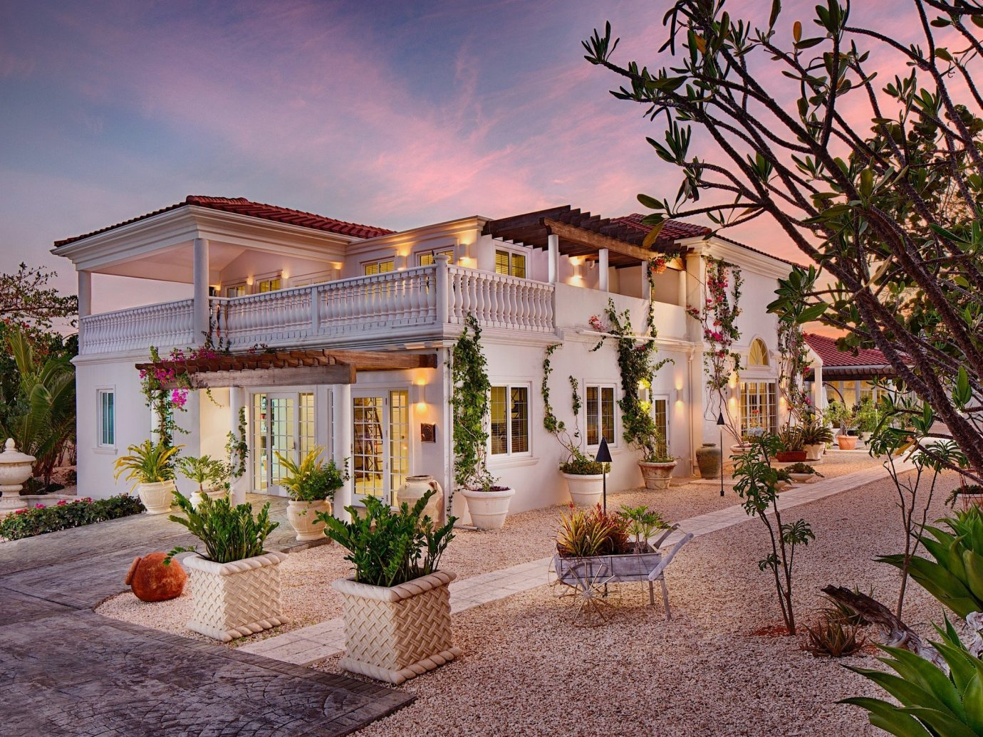 Hotels tree ground outdoor house property estate home residential area neighbourhood plant mansion vacation Courtyard real estate Villa Resort facade hacienda Village backyard cottage stone several