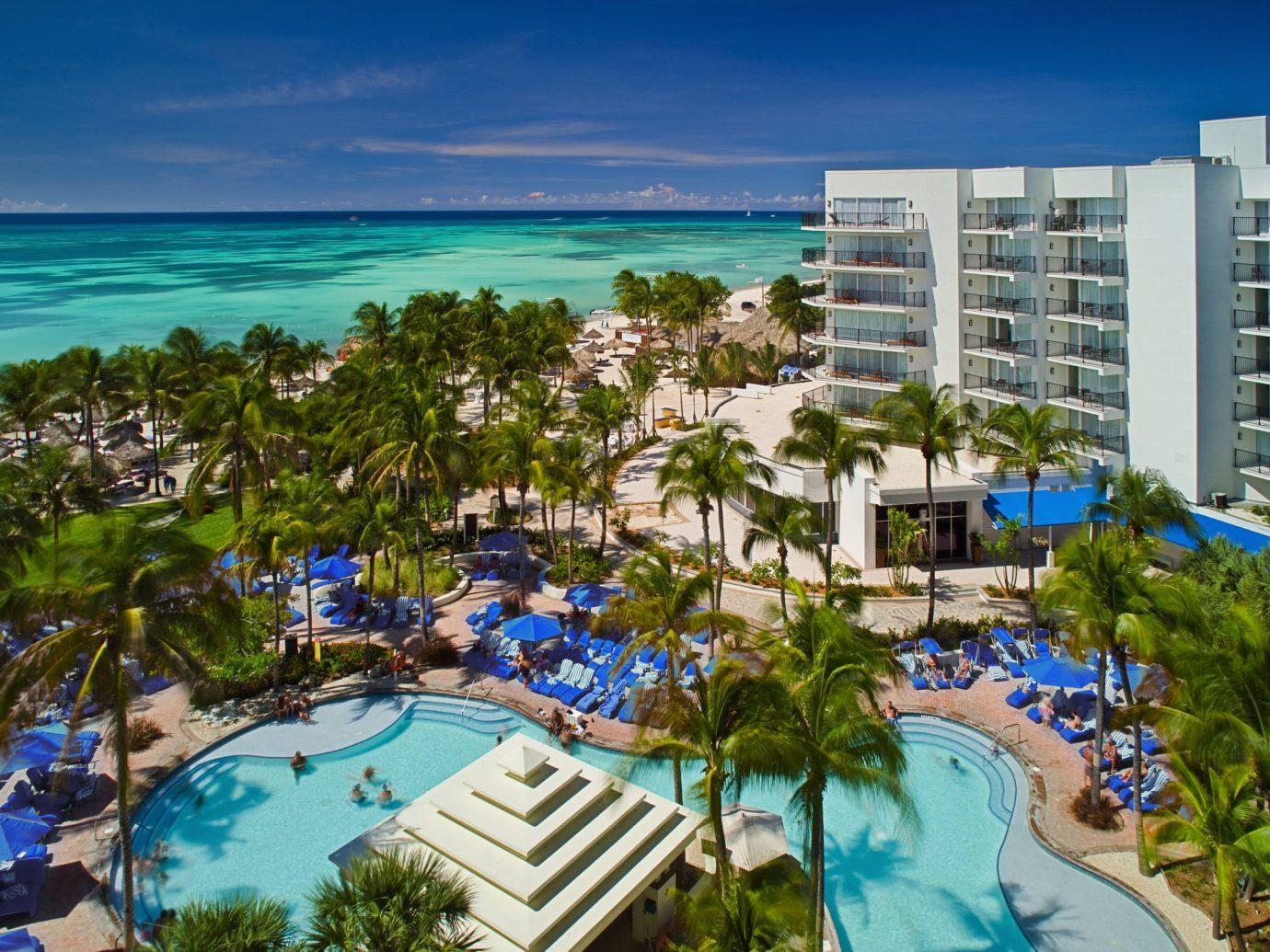 Aruba caribbean Hotels Resort leisure resort town swimming pool vacation tourism condominium hotel real estate mixed use palm tree arecales tropics City sky tree water recreation bay